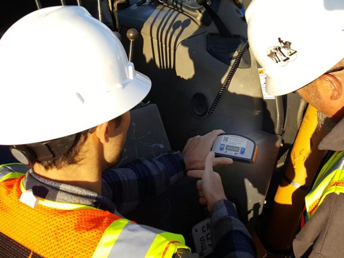 Two Hydromax USA workers examine a UtilAlert unit together.
