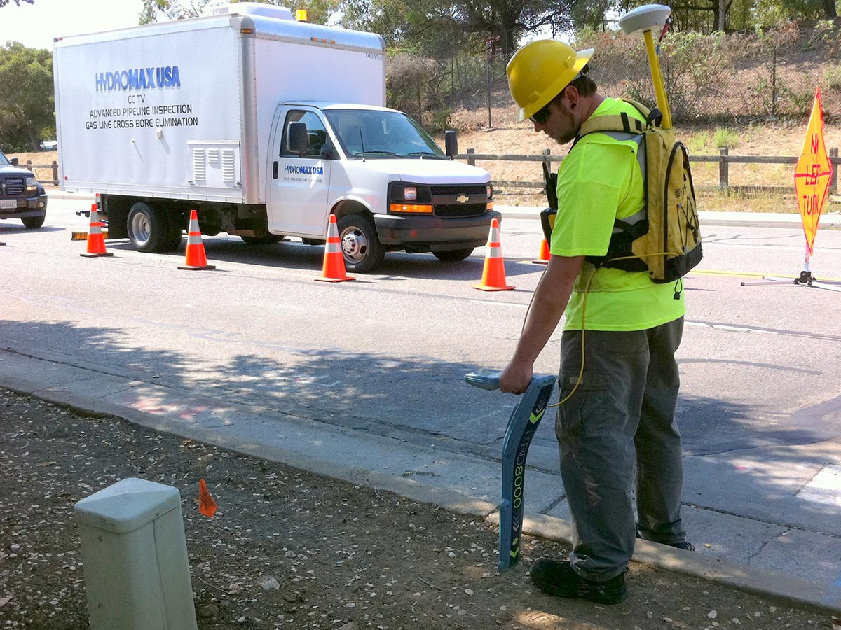 A HydroMax USA worker operates a backpack sensor along a roadside with a Hydromax CCTV Inspection truck in the background.