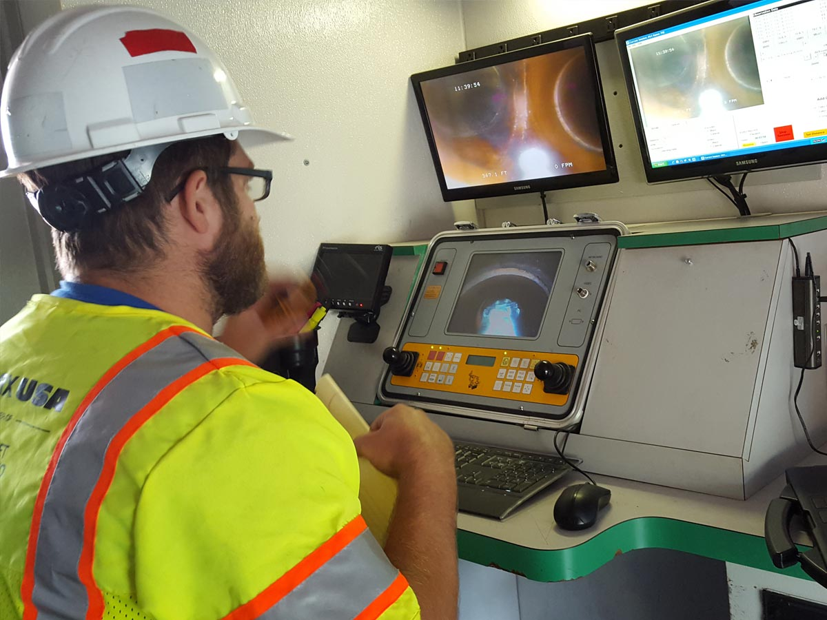 A Hydromax worker using a specialized computer console to monitor the inside of a pipeline.