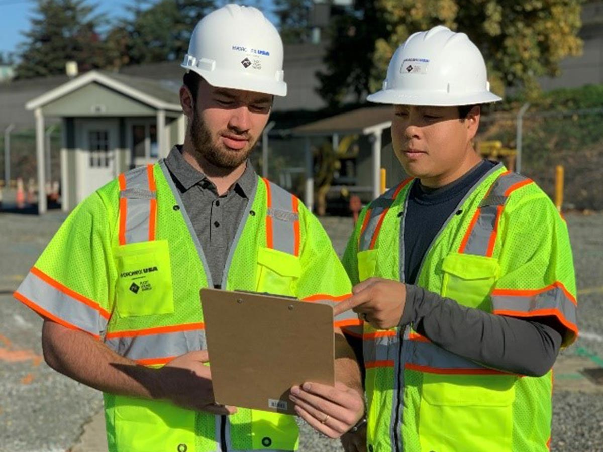 Two Hydromax USA workers consult a clipboard together.