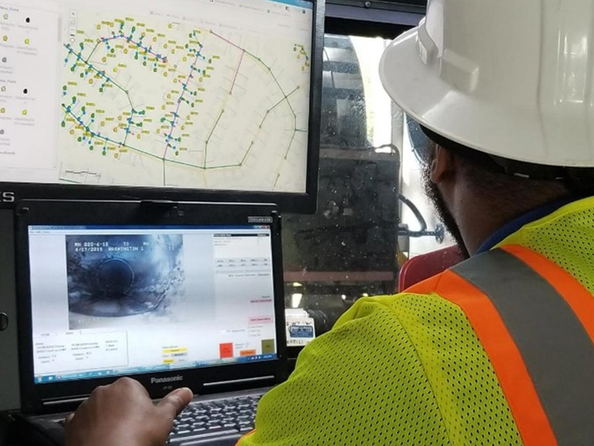 A Hydromax USA worker monitoring video from inside a pipeline and a utility map side-by-side.