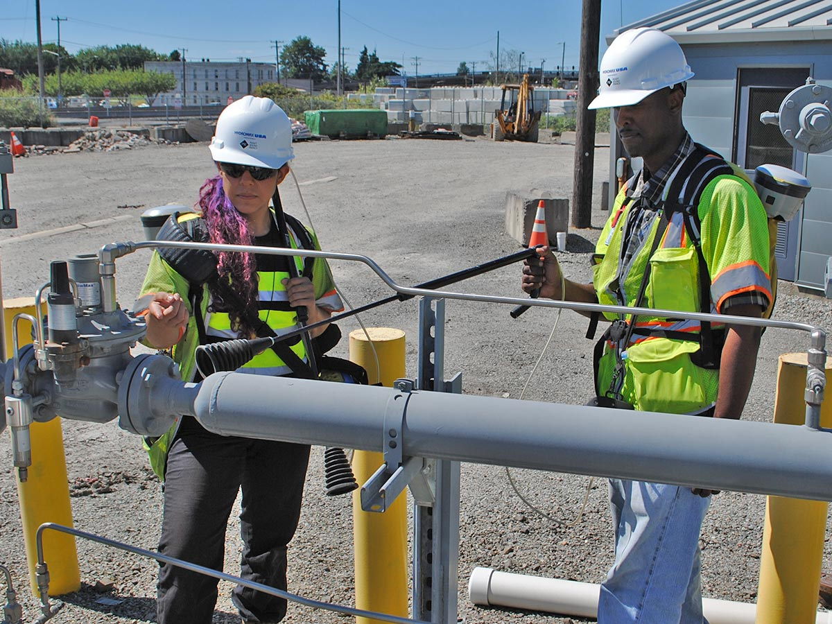 Two Hydromax USA workers check a gas valve with a sensor.