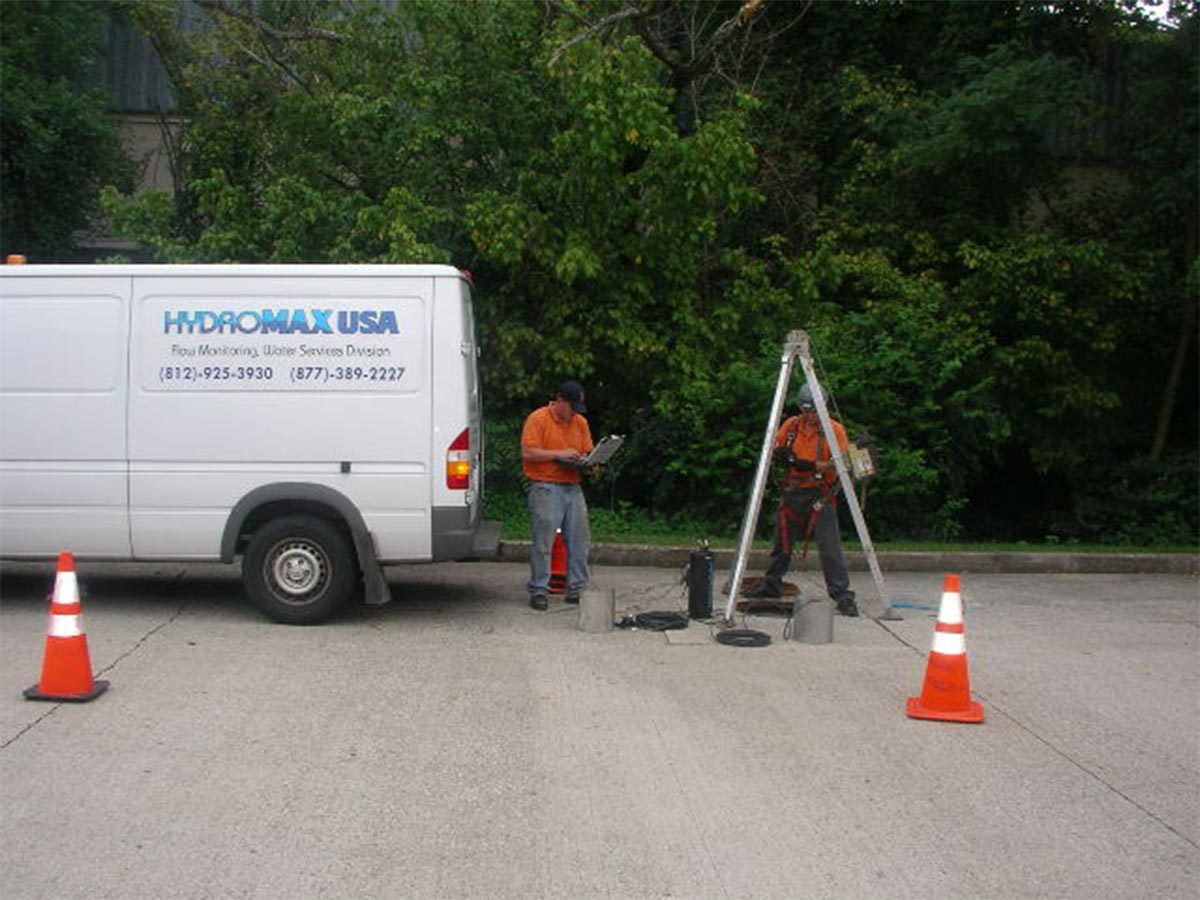 Two HydroMax USA employees working over a manhole, preparing to install a Flow Monitor.