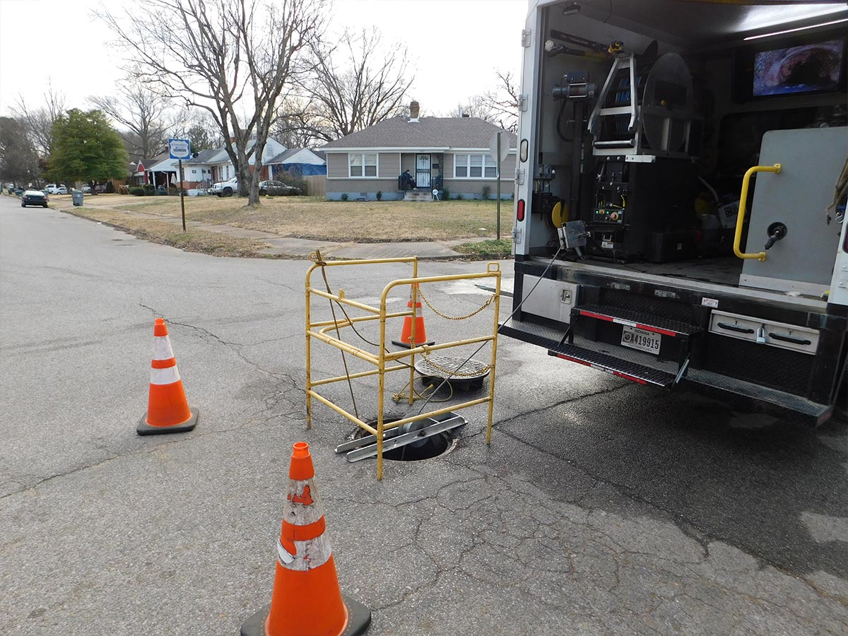 A manhole that has been cordoned off behind a HydroMax USA truck in preparation for an inspection.