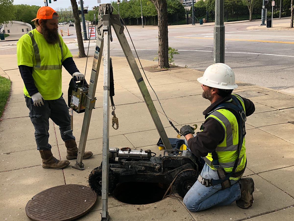 Two HydroMax USA workers working on a manhole during an inspection.
