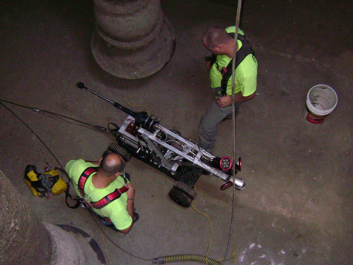 Two Hydromax workers inside a sewer system, examining a wheeled sensor drone during an inspection