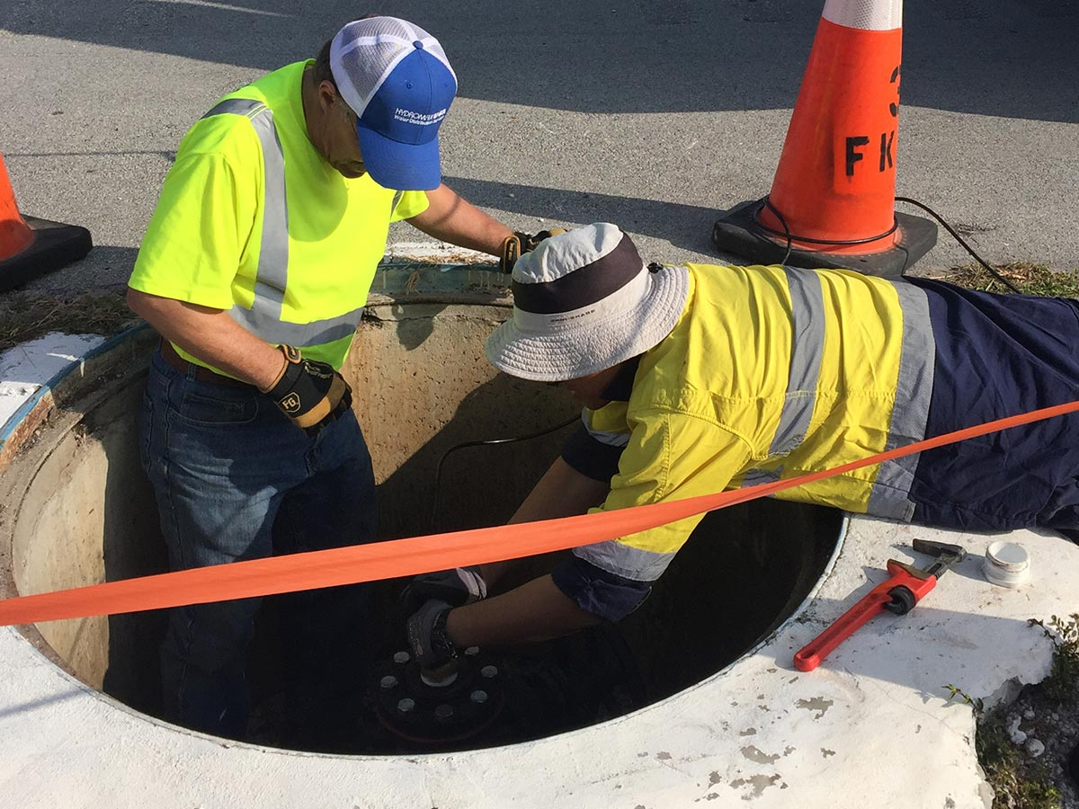 Two Hydromax USA workers working in a shallow manhole that has been cordoned off for safety.