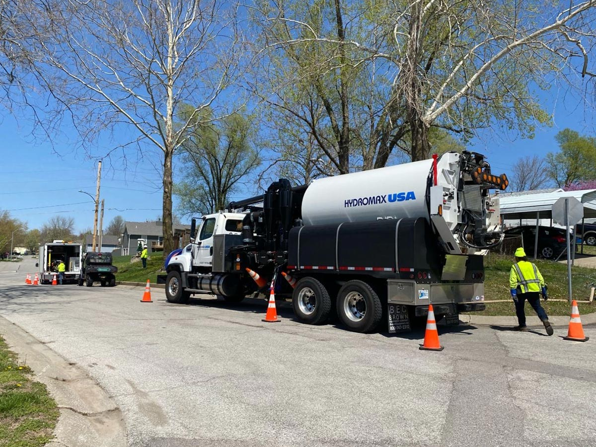 A Hydromax USA truck set up on a street, surrounded by safety cones.