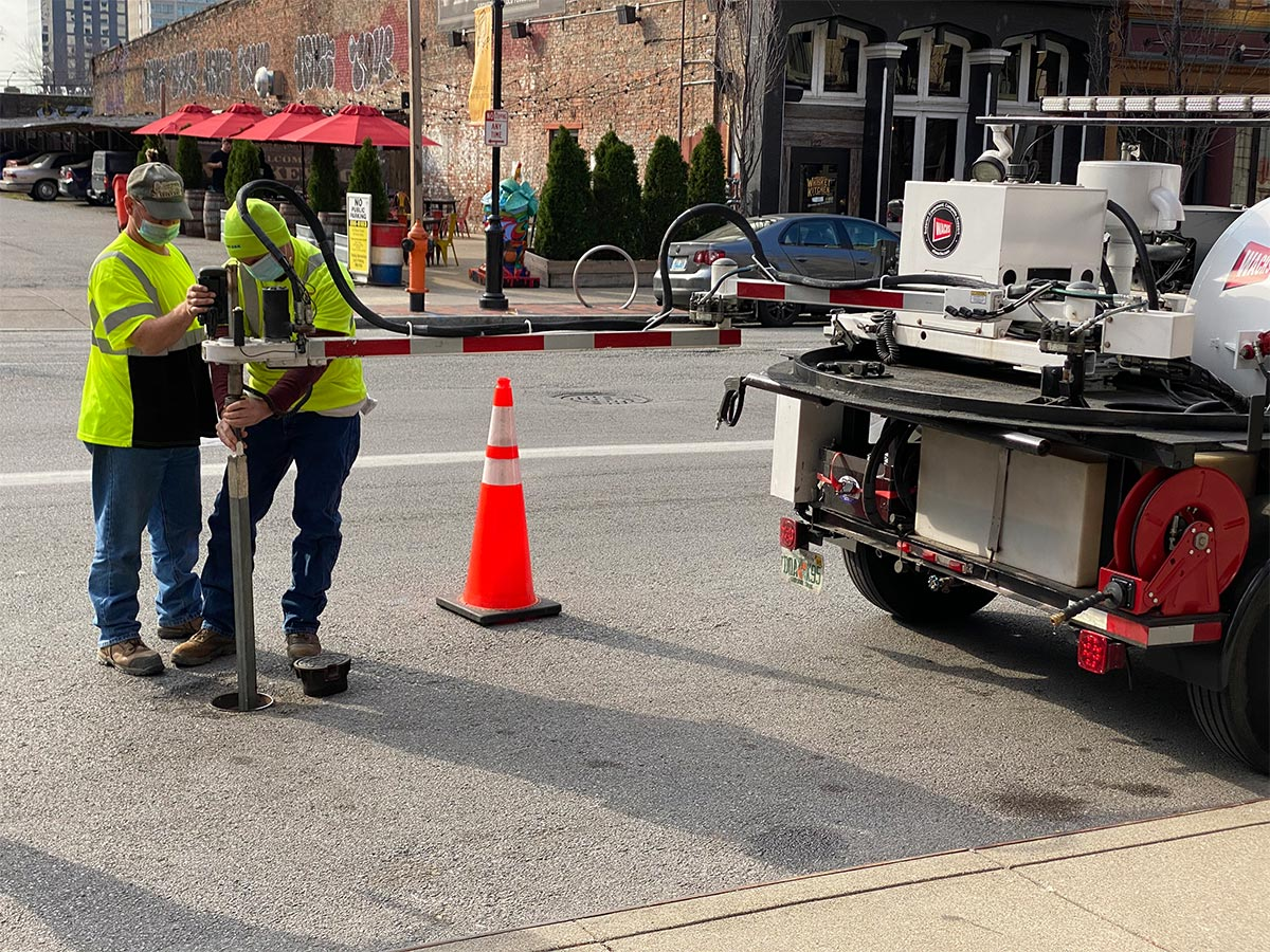 Two HydroMax USA workers insert a probe from their truck into a utility valve on the street.
