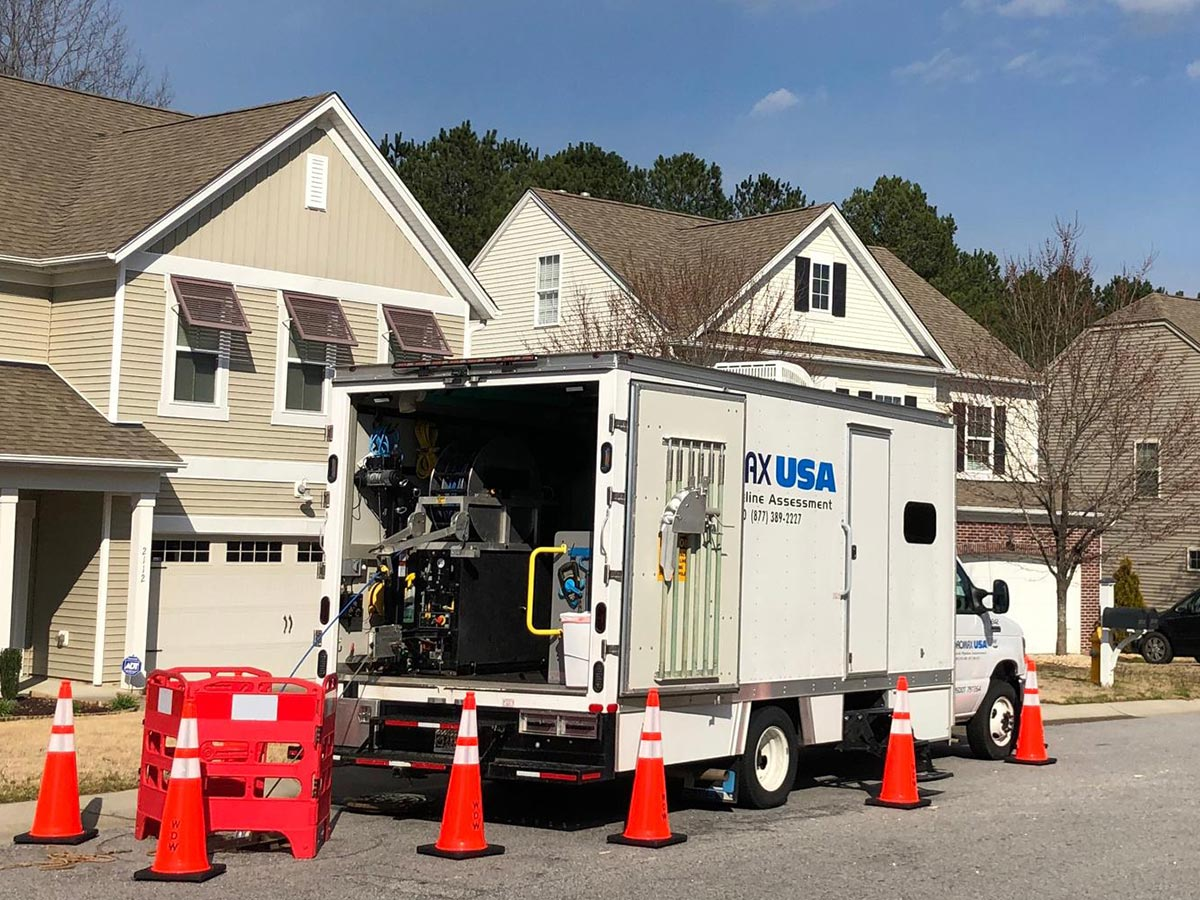 A Hydromax USA CCTV inspection truck parked on a street by a manhole, surrounded by safety cones.