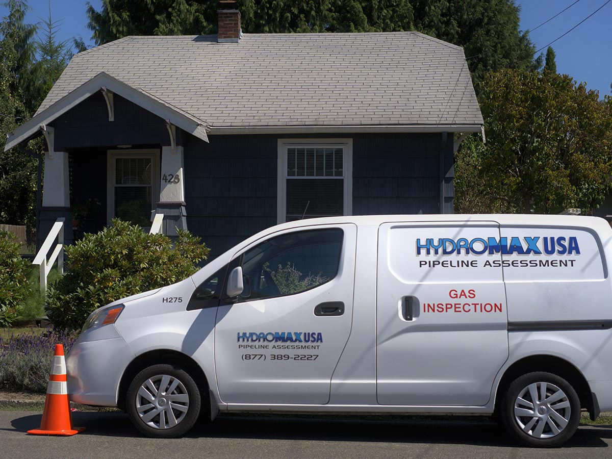 A Hydromax USA gas inspection van parked in front of a house.